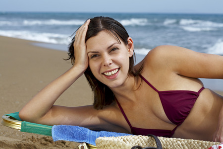 basking: Young woman in bikini on beach lying in deck chair sea in background.