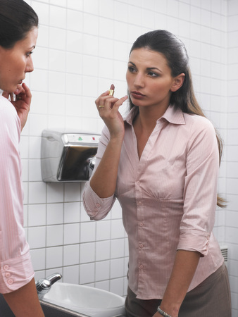 grooming: Woman reflected in office washroom mirror applying make-up
