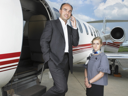 three persons only: Businessman exiting private jet next to flight attendant.