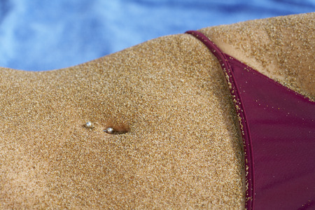Close up of sandy belly piercing in belly button bikini bottom in section.