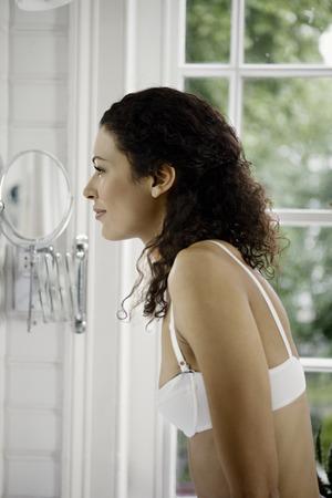 selfish: Woman looking in mirror. LANG_EVOIMAGES