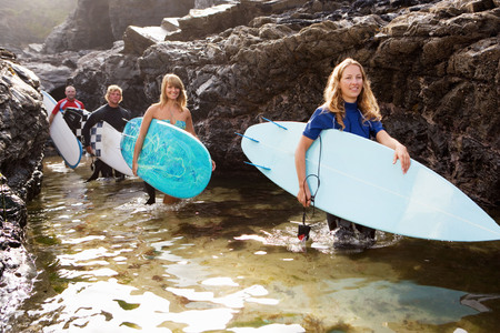 Four people carrying surfboards by large rocks smiling. LANG_EVOIMAGES