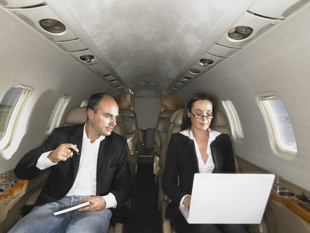 three persons only: Businesswoman and businessman in private jet having a discussion.