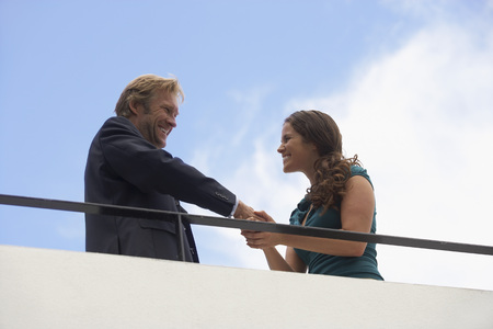 Young businessman and business woman on balcony. LANG_EVOIMAGES