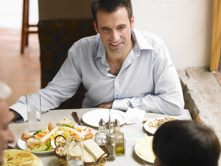 enjoys: Boy (8-10) sitting at café table with father and grandfather (differential focus)