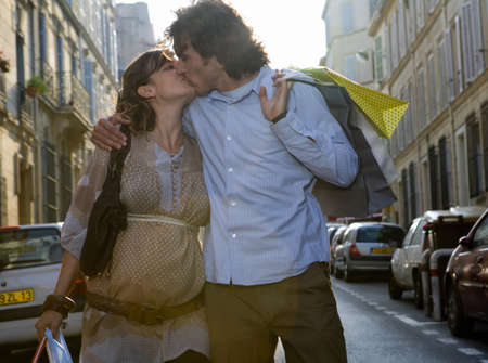passtime: Pregnant young woman and young man kissing in street