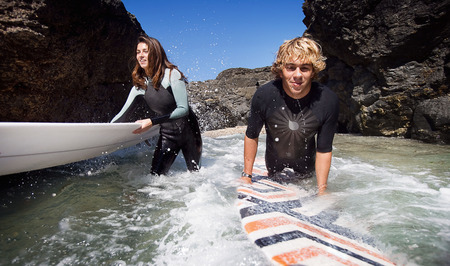 Couple standing in water with surfboards smiling.
