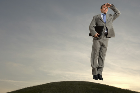 docklands: Businessman hovering above hill looking at horizon LANG_EVOIMAGES