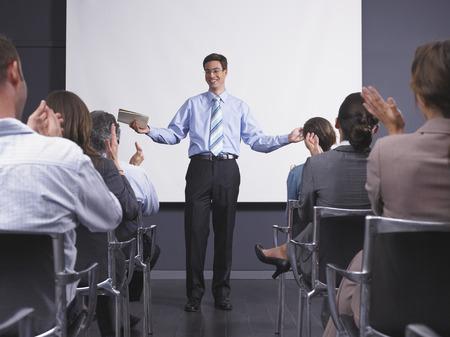 fill in: Man giving speech in presentation room