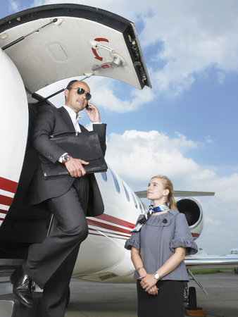Businessman exiting private jet beside stewardess. LANG_EVOIMAGES