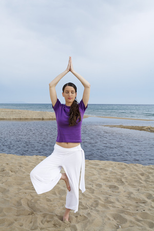 Woman doing yoga on beach with eyes closed. LANG_EVOIMAGES