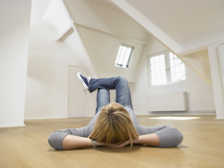 Woman resting on her back on the wooden floor of empty white loft. LANG_EVOIMAGES