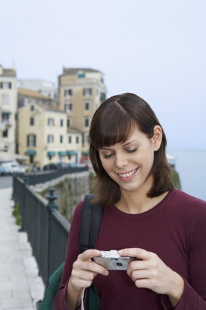 ruck sack: Young woman portrait with camera looking at display smiling old city in background.