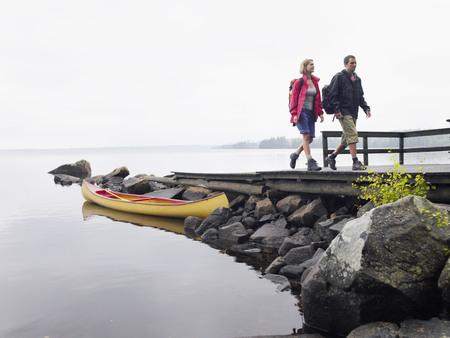 ruck sack: Couple walking on dock near a boat.