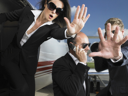 three persons only: Two bodyguards defending businessman while exiting jet. LANG_EVOIMAGES