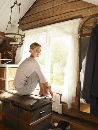 sweden resting: Businesswoman sitting on trunk in home office LANG_EVOIMAGES