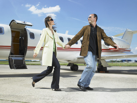 Happy couple running out of private jet.