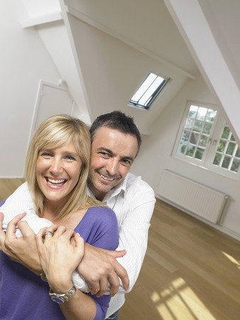 Happy couple holding each other into white empty loft. Portrait.