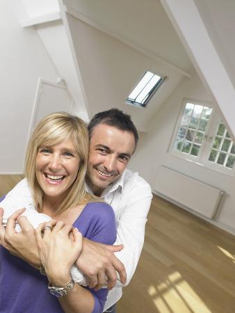 multi age: Happy couple holding each other into white empty loft. Portrait.