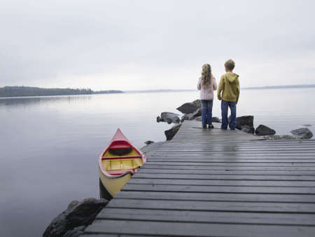 safe water: Young girl and young boy standing on a dock near a boat.