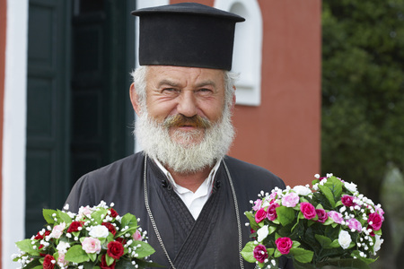 Old priest in front of church holding two bunches of flowers looking into camera smiling.