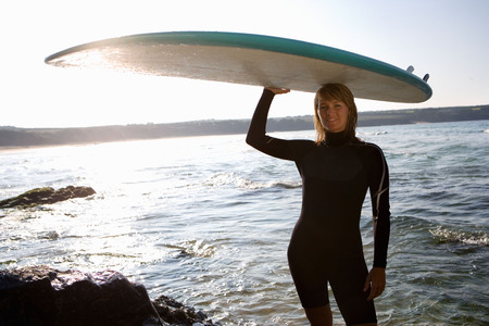 Woman standing with a surfboard over her head.