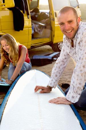 waxes: Couple waxing surfboards near a van.