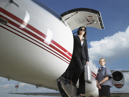 Businesswoman exiting private jet next to flight attendant. LANG_EVOIMAGES
