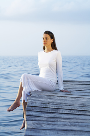cross legs: Young woman sitting on dock looking at sea. LANG_EVOIMAGES
