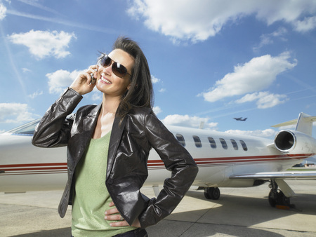 Woman standing next to private jet on phone.