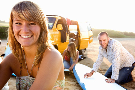 waxes: Woman on the beach smiling with couple waxing surfboards in background.