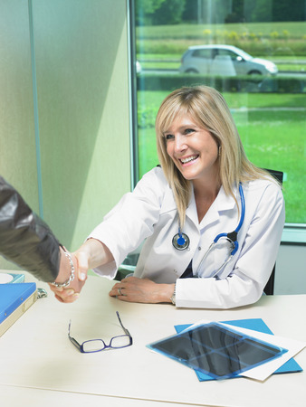 Female doctor at her desk shaking hand with patient.