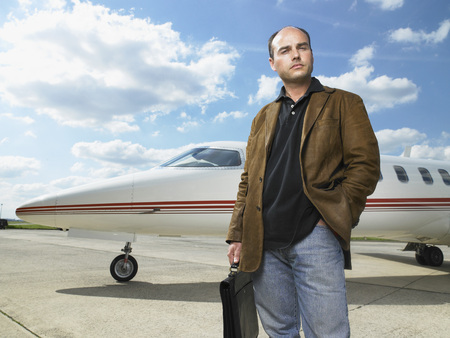 Man standing in front of private jet.