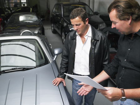affluent: Two men in a garage discussing a sale.