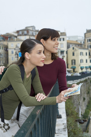 ruck sack: Two young women with map looking into distance smiling old city in background.