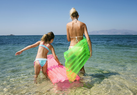 Woman with young girl at the beach with inflatable rafts. LANG_EVOIMAGES