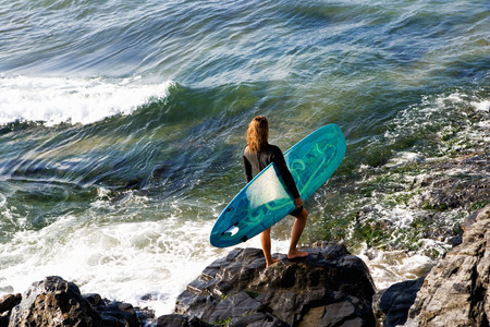 Woman standing with a surfboard on large rocks.