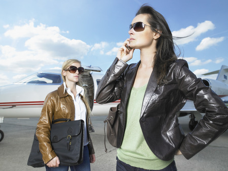 Two businesswomen standing in front of jet. LANG_EVOIMAGES