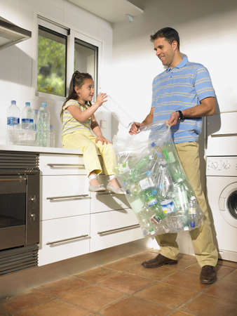 selections: Father and daughter (4-6) sharing recycling duties in  kitchen