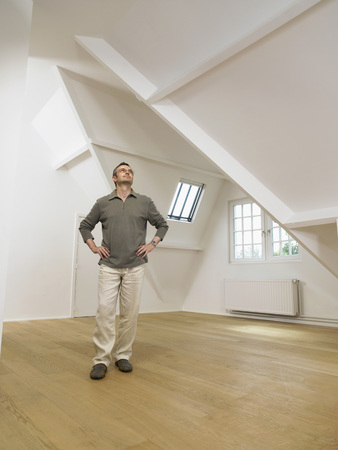 Man looking up inside empty white loft.