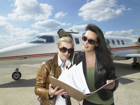 Two businesswomen working in front of private jet. LANG_EVOIMAGES