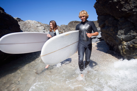 two persons only: Couple running in water with surfboards smiling. LANG_EVOIMAGES