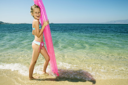 Young girl holding up an inflatable raft at the beach smiling.