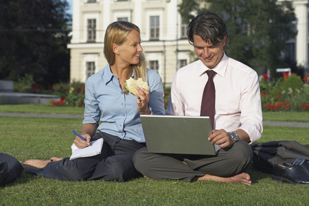 appointment book: Businessman and businesswoman sitting in park working. LANG_EVOIMAGES