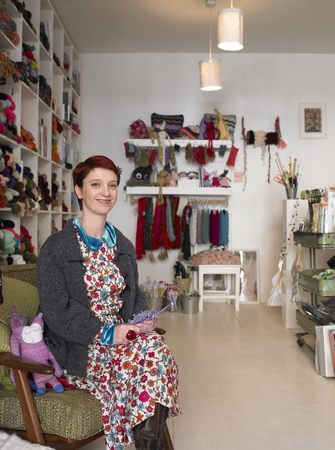 proprietary: Woman sitting in craft shop, smiling, portrait LANG_EVOIMAGES