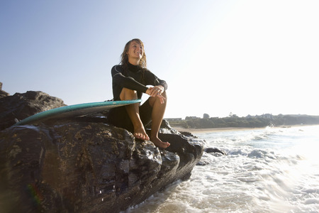 Woman sitting on large rocks with surfboard smiling.