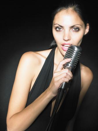 vocalist: Female singer with microphone elegant black dress portrait.