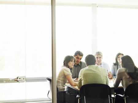 encounters: Colleagues in meeting, view through doorway