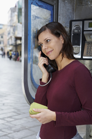 payphone: Young girl on public phone wallet in hand smiling city in background.