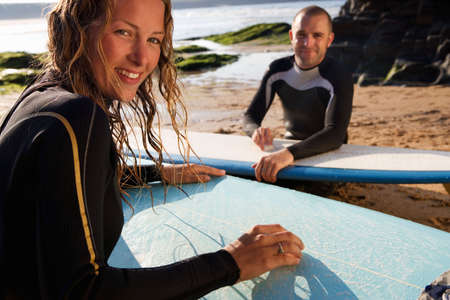 two persons only: Couple waxing their surfboards smiling.